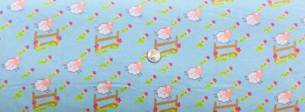 Flannel!! Fluffy sheep jumping over the fence on light blue. MDG - Fabric by the yard