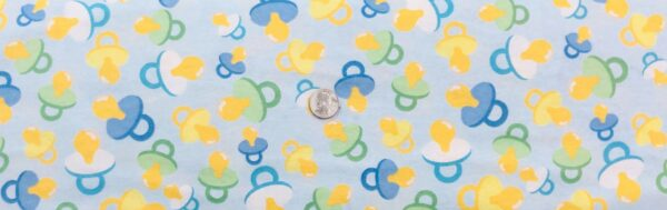 Flannel!! Baby pacifiers in pastel yellow, green and blue all over light blue. MDG - Fabric by the yard