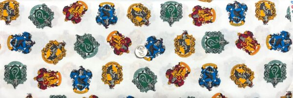 Harry Potter badges toss. Gryffindor. Hufflepuff. Ravenclaw. Slytherin. Camelot Fabrics 23800228 - Fabric by the yard